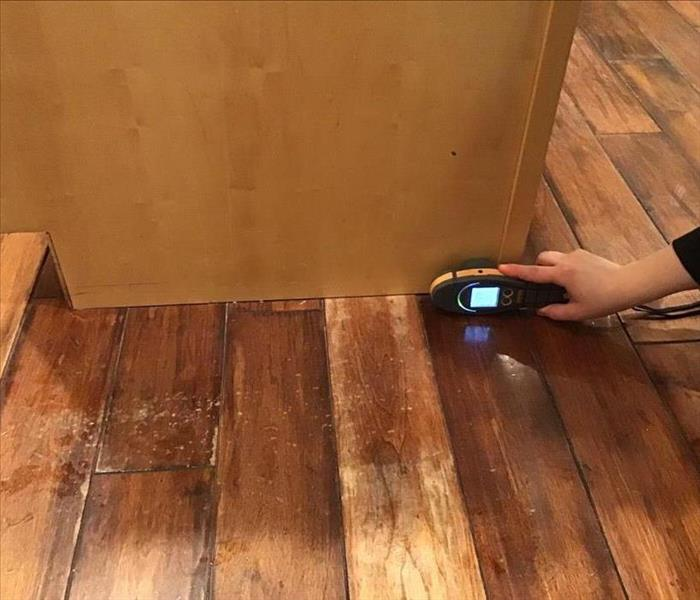 Wet brown wood floor with a brown cabinet.  Yellow & black Moisture meter at the bottom of the cabinet.