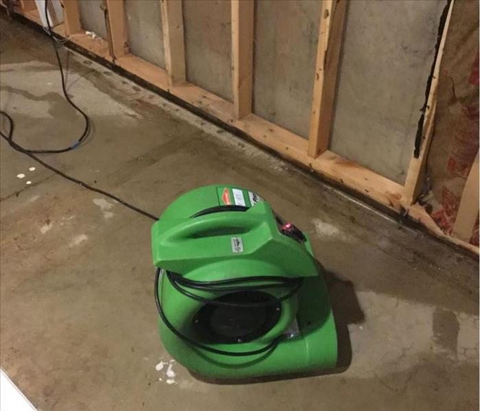 Green air mover on a wet concrete floor with brown studs on the wall.